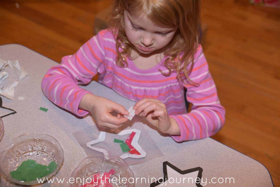 Young girl putting colored paper on Con-tact paper