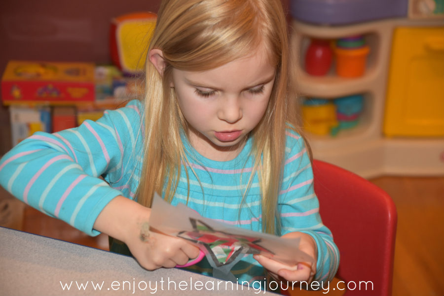 Young girl cutting out Christmas star paper craft