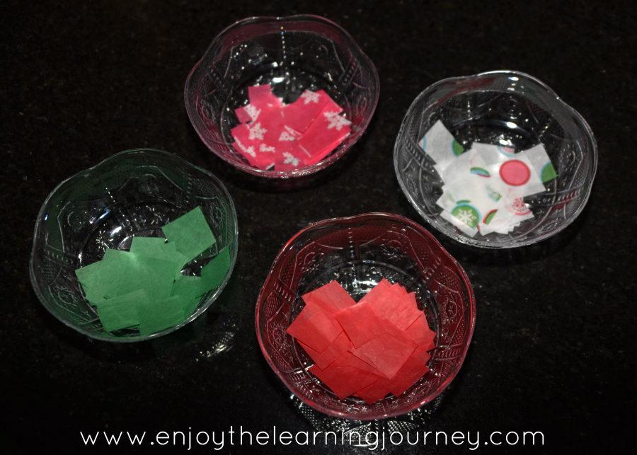 Colored paper pieces in bowls on table